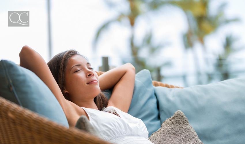 Feng Shui tips for summer article, July 06 2021, in-post image. Woman relaxing outside of home on patio furniture.
