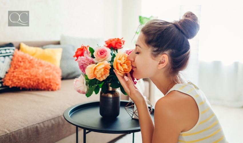 Interior decorating course article, July 22 2021, in-post image, woman happily smelling flowers in vase on living room coffee table