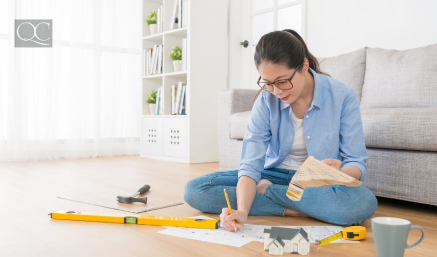 Feng Shui consultant sitting in living room wooden floor using palette tool choosing color for design house interior.