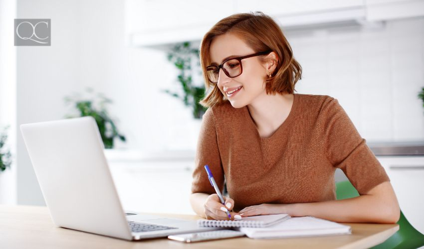Woman on remote work or online education, using laptop computer, making notes, indoors at office or home at daytime. Online business, young professional at workplace. Working from home.