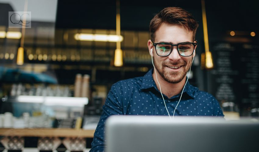 Businessman sitting in a restaurant listening to music while working on a laptop. Smiling man wearing earphones managing business work on laptop sitting in a cafe.