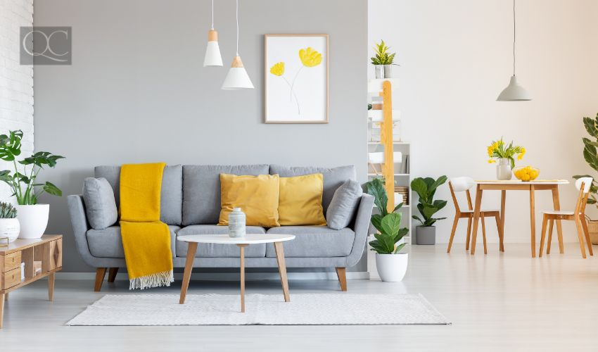 Orange blanket on grey sofa in modern apartment interior with poster and wooden table.