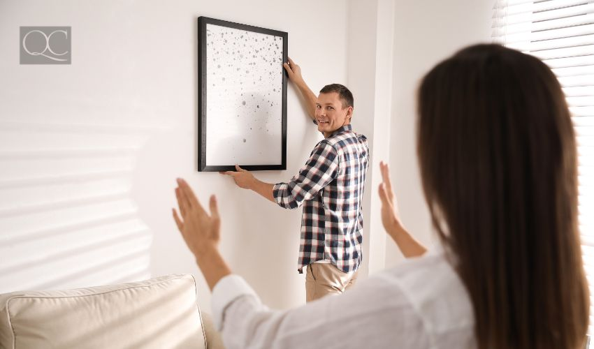 Home staging jobs article, Aug 25 2021, in-post image 3. Happy couple decorating room with picture together. Interior design.