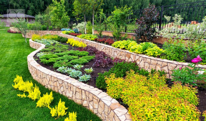 Landscape design of nice home garden, natural landscaping with decorative stones in residential house backyard. Luxury flowerbed and beautiful landscaping in summer, green landscaped yard.