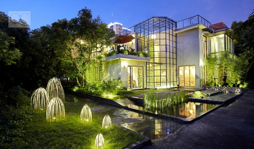 Outdoor landscape of big, beautiful home at night