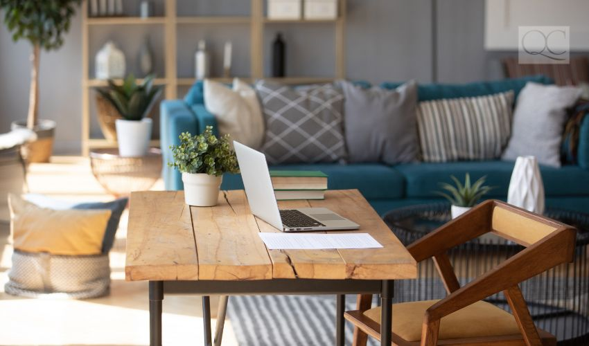 Sunlight illuminates living room workplace home office interior for comfort productive work, brown and blue colours. On wooden table laptop comfy couch with cushions on background, workday end concept
